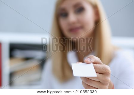 Smiling businesswoman holding hand in white shirt give blank calling card. White collar partners company name exchange executive or ceo introducing at conference product consultant sale clerk concept