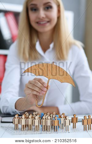 Smiling Business woman in hand holds a miniature umbrella in the hand of the topic of liability insurance