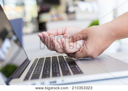Woman Holding And Pressing Or Touching Her Hand While Working With Laptop In The Office. Numbness Or