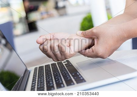Woman Holding And Pressing Or Touching Her Wrist While Working With Laptop In The Office. Numbness O