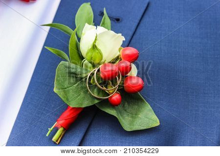 wedding rings on boutonniere on lapel of jacket of groom