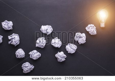 Top View Crumpled Paper And Light Bulbs On Black Stone Board. Create Idea Concept