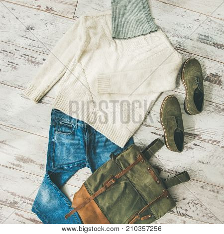 Flat-lay of Fall lady' s clothes outfit. Ecru colored knitted woolen sweater with braids, blue denim jeans, haki suede oxford boots, large backpack, cap over parquet background, top view, square crop