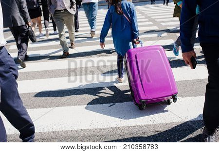 The girl drags a suitcase on wheels in the city on the crosswalk among people