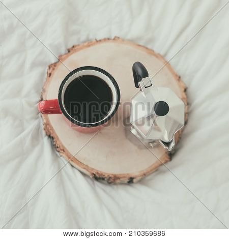Coffee mug with steel coffee maker on wooden tray on white bed sheet. Top view. Flat lay