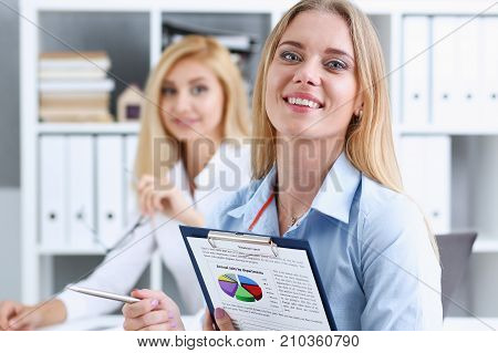 Beautiful business woman portrait. Holds a clipboard with financial statistics fashion style mulatto curly hair with white locks eye view of the camera