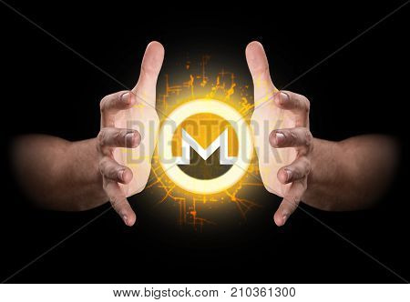 A pair of male hands reaching through the dark grasping at a monero coin hologram poster