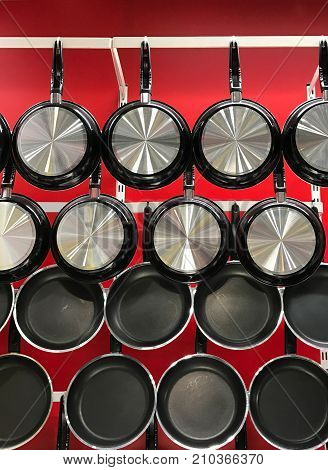 Hanging teflon pans on red wall in kitchenware store