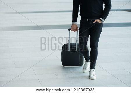 Man walking with wheeled bag at airport terminal and talking on phone