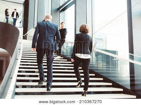 Modern business people walking on stairs in glass hall of office building