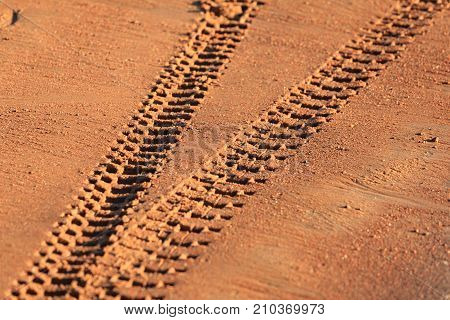 Traces of tire treads on orange sand diverging in different directions.