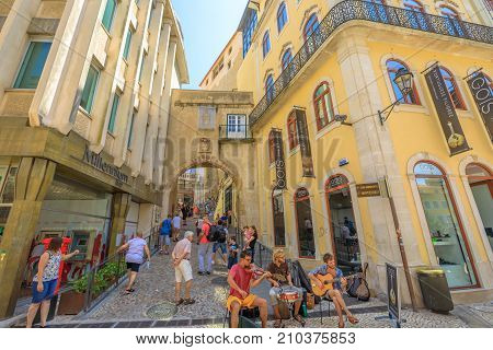 Coimbra, Portugal - August 14, 2017: people walk through Tower and Arch of Almedina, the iconic Archway of Almedina, fortification of Manuelino period in historic medieval Coimbra, Central Portugal.