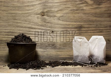 Dry Tea Leaves For Black Tea And Paper Tea Bag On Wooden Background