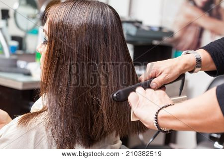 Stylist Using Flat Iron On Hair Of Female Client Sitting In Salon Chair