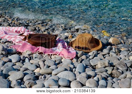 Straw hat, sunglasses, towel, bag on a background seascape with a pebble beach