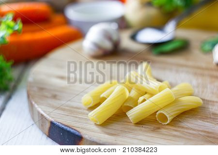 Italian pasta rigatoni over the wooden board