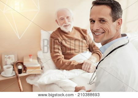 My patient. Cheerful pensioner holding hands together and feeling happiness while talking to his doc