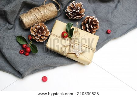 Christmas festive styled stock image composition. Handmade Christmas gift box, red berries, pine cones isolated on grey linen blanket. Top view. Winter holiday background. Winter concept.