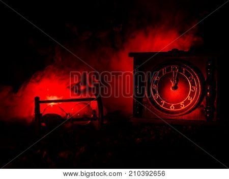 Time Concept. Silhouette Of Hourglass Clock And Old Vintage Wood Clock With Arrow And Smoke On Dark