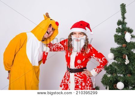 Happy young woman in santa claus hat and man in carnival costume of deer. Fun, holiday, joke and christmas concept.