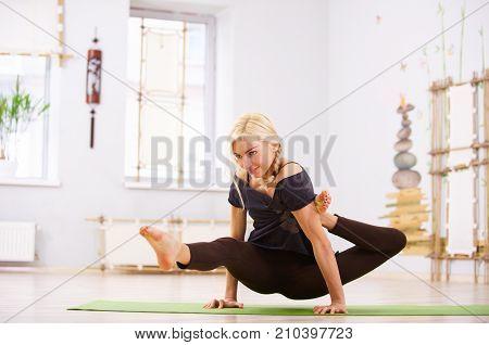 Beautiful sporty fit yogi woman practices yoga asana Eka Hasta Bhujasana pose in the yoga class