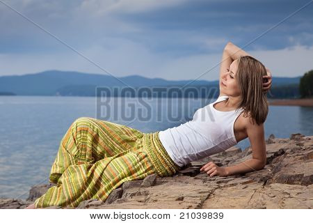 Beautiful happy woman sitting on rock over sea at summer storm day