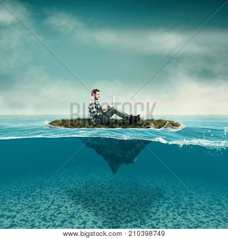 Business man work on laptop sitting on a piece of land floating in the ocean. Split half-water seascape.