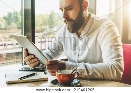 Young bearded businessman sits in cafe at table, holding tablet computer, working.On table cup of coffee, notebook, smartphone.Man is working