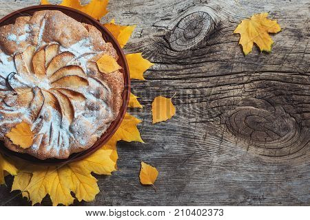Fresh pastry apple pie charlotte on wooden table background decorated with yellow autumn leaves. Fall Food Cook Cuisine Homemade Rustic concepts. Holiday dinner Copy space Flat Lay