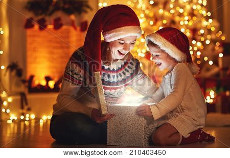 Merry Christmas! family mother and child with magic gift at home near Christmas tree and fireplace