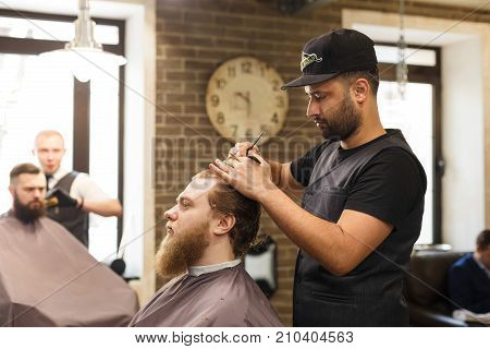 Man getting hipster haircut by man hairstylist at barbershop. Stylish barber and client. Male Barbershop