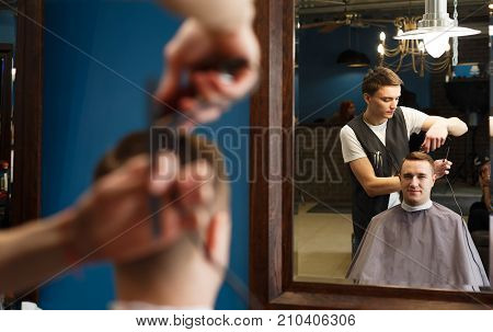 Barber with trimmer making haircut at barbershop. Client looking at mirror. Modern barbershop for men