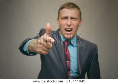 Angry business man in a suit swears and screams at someone and pointing at him with his index finger. Strict angry boss. Man proves his rights.