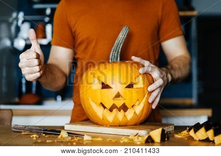 man carved a scary face in a pumpkin for a Halloween holiday.