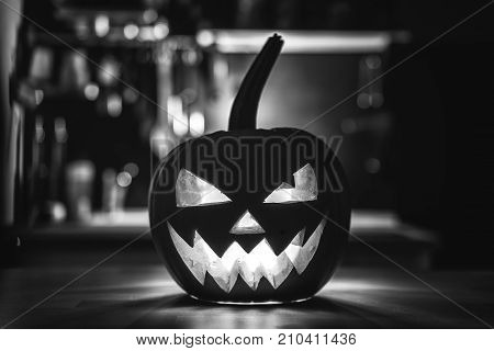 black and white glowing pumpkin with a terrible face jack. Concept Halloween.