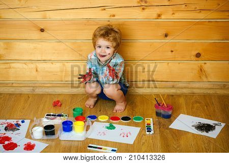 Imagination creativity and freedom concept. Boy painter painting on wooden floor. Arts and crafts. Child showing tongue with colored hands gouache paints and drawings. Kid learning and playing.