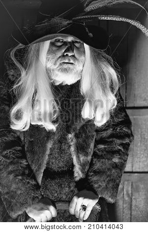 Druid old man with long grey hair beard in hunter hat with bird feathers and fur coat leans on deer antlers on dark background