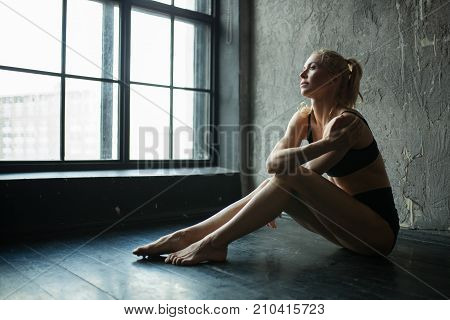Fit Woman In Profile Sitting On Floor In Loft Gym