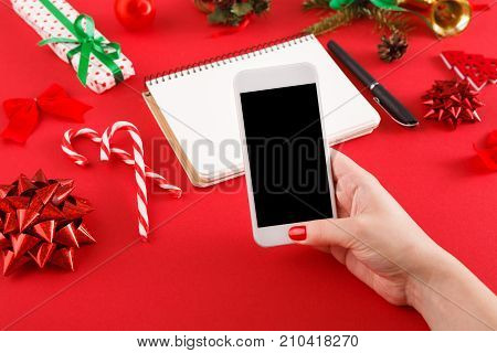 Christmas online shopping background. Female hand holding smartphone with empty screen for copy space at messy red table surface with notepad for wish or purchase list