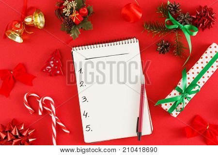 Christmas wish list or letter to Santa. Notepad with copy space on red messy table background. Preparing for winter holidays, top view
