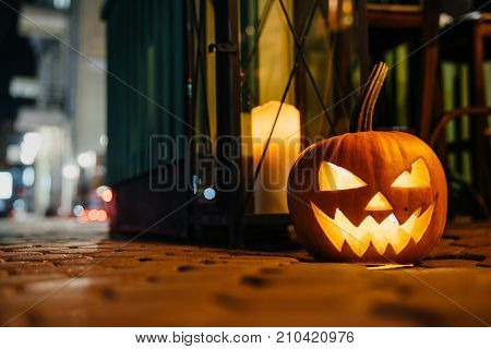 Halloween concept. The head is a pumpkin with a terrible face on the floor of the pedestrian street in the city.