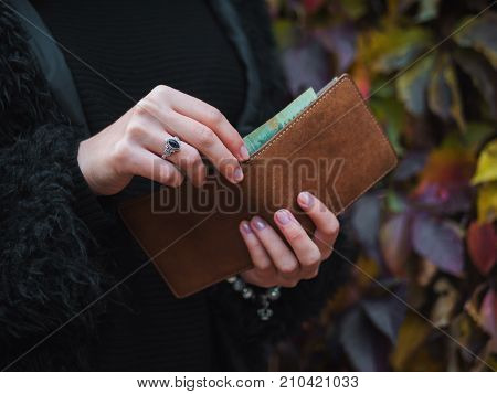 people saving and finance concept - hands with cash money and wallet in autumn park. Close up hands of young woman with brown purse.