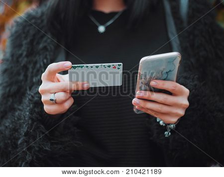 Online paymentWoman's hands holding smartphone and using credit card for online shopping in autumn park