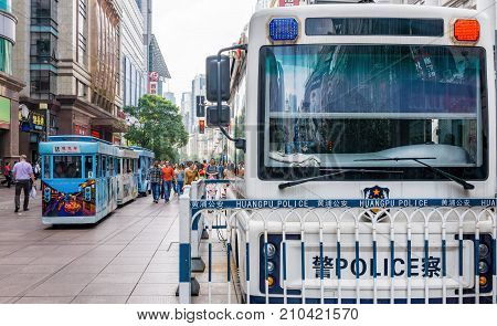 Shanghai, China - Nov 6, 2016: On Nanjing Road Pedestrian Street - Modern buildings in western architectural designs line the metropolitan area. Huangpu police van to maintain public peace and order.