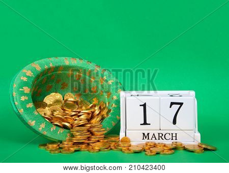 Wood blocks showing calendar date March 17th Saint Patrick's Day sitting on green background leprechaun hat with gold coins spilling out next to blocks.