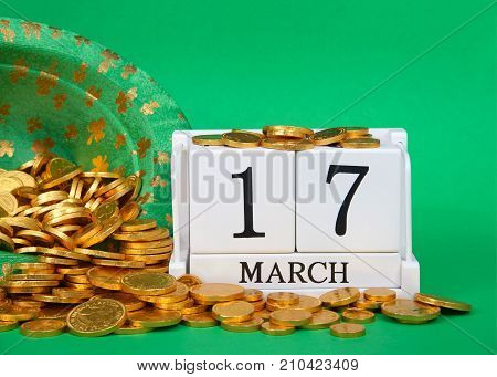Close up on wood blocks showing calendar date March 17th Saint Patrick's Day sitting on green background leprechaun hat with gold coins spilling out next to blocks.