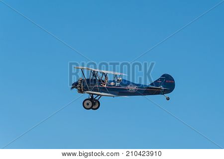 EDEN PRAIRIE MN - JULY 16 2016: 1929 Curtis-Wright Travel Air E-4000 biplane flies in blue sky at airshow. This biplane is flown by a MN based company for historic flight experiences by passengers.