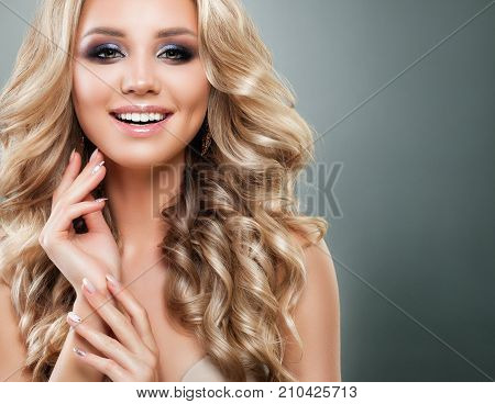 Beautiful Blonde Woman with Long Healthy Wavy Hair and Makeup Smiling. Perfect Girl for Beauty Salon Background. Blondie Fashion Model with Permed Hairstyle Make up and Manicered Hands on Background with Copy space