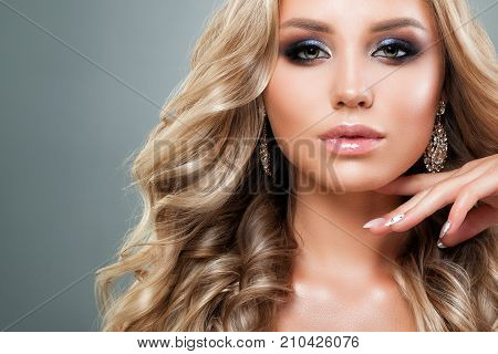 Beautiful Blonde Woman with Healthy Wavy Hair. Blondie Fashion Model Girl with Shiny Hairstyle Perfect Makeup and Manicered Nails