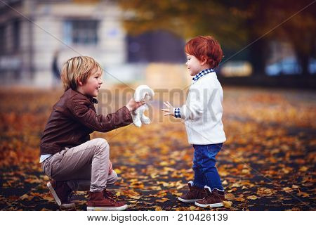 cute fashionable brothers kids boys playing together in autumn park